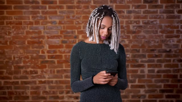 Young-African-girl-with-dreadlocks-using-a-smartphone-looking-at-the-camera-and-smiling-Brick-wall-in-the-background-