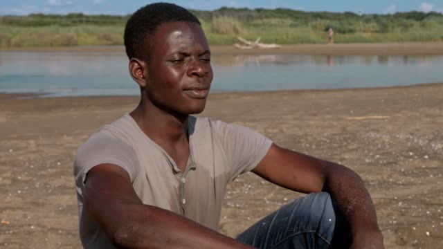 Pensive-upset-black-african-man-alone-on-the-beach--missing-family-home