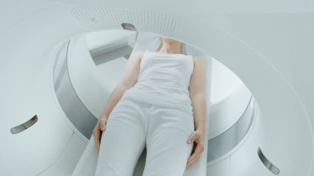 Female-Patient-Lying-on-a-CT-or-MRI-Scan-Bed-is-Moving-inside-Machine-Scanning-Her-Body-and-Brain-In-Medical-Laboratory-with-High-Tech-Equipment-Elevated-Camera-Shot-