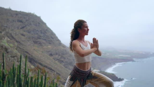 Joven-es-practicar-yoga-en-el-lago-de-la-montaña