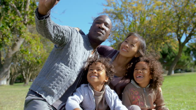 Happy-Multiethnic-family-taking-selfie-on-smartphone