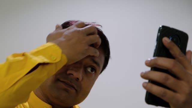 Narcissistic-man-looking-at-his-smart-phone-camera-at-himself-and-making-and-adjusting-his-black-hair