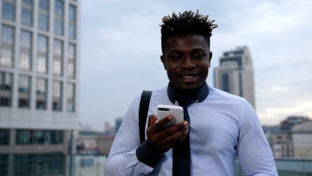 Dark-skinned-businessman-chatting-online-on-phone