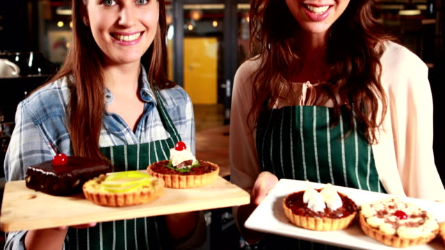 Smiling-waitresses-showing-cakes