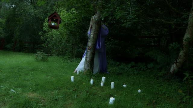 4k-Fantasy-Schuss-eine-Fee-und-versteckt-sich-hinter-einem-Baum-totale