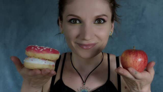 4k-Shot-of-a-Woman-Posing-in-Studio-with-Donut-and-Apple
