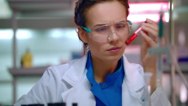 Mujer-química-haciendo-pruebas-químicas-en-el-laboratorio-de-química-Químico-trabajando