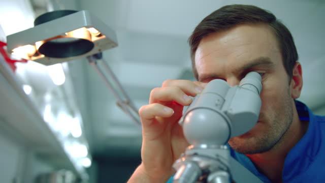 Microscopio-médico-masculino-Cerca-de-un-médico-científico-mirando-a-través-del-microscopio
