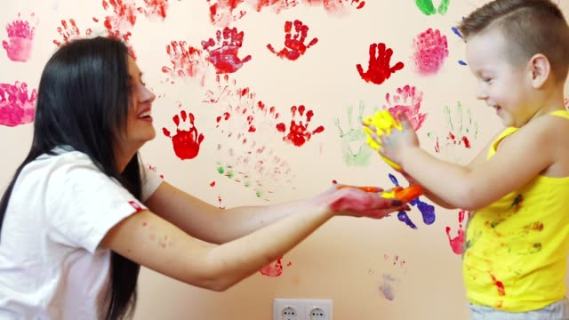 Happy-mother-and-her-cute-boy-having-fun-together-leaving-their-colorful-handprints-on-the-wall-Young-happy-family-Mother-and-child-concept