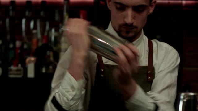 Joven-guapo-barman-en-la-barra-interior-agitando-y-mezclando-alcohol-coctel