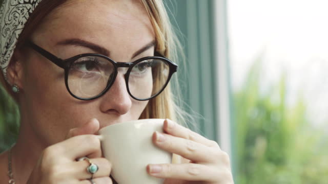 Beautiful-young-woman-drinking-coffee-in-cafe-Girl-dreaming-Female-wearing-glasses-