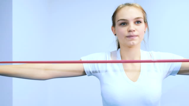 A-girl-is-training-her-hands-with-a-rubber-bandage