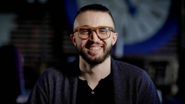 Portrait-of-handsome-positive-hipster-looking-at-the-camera-and-smiling-Stylish-man-in-blue-jacket-and-fashionable-eyeglasses-staring-before-him-trying-to-be-serious-removing-his-eyes-and-laughing