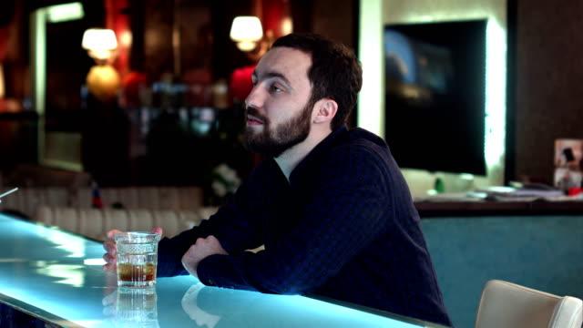 Hombre-joven-en-un-bar-tener-una-conversación-con-el-camarero-y-beber