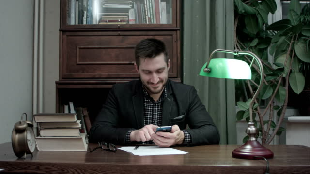 Young-writer-at-his-desk-happily-messaging-on-mobile-phone