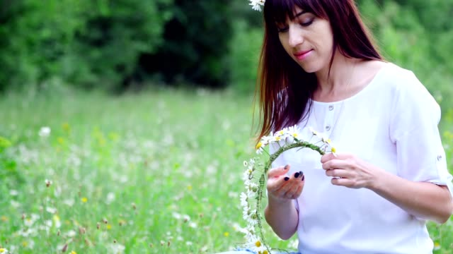 Summer-amidst-a-chamomile-lawn-in-a-forest-a-young-woman-a-brunette-weaves-a-wreath-of-chamomiles
