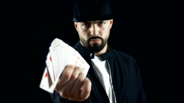 Professional-Street-Magician-in-a-Cap-Performing-Sleight-of-Hand-Card-Tricks-Fan-Out-Cards-Spinning-One-Card-on-a-Finger-Background-is-Black-