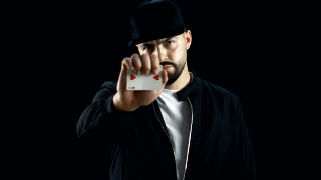Professional-Street-Magician-in-a-Cap-Performs-Impressive-Sleigth-of-Hand-Card-Trick-Background-is-Black-