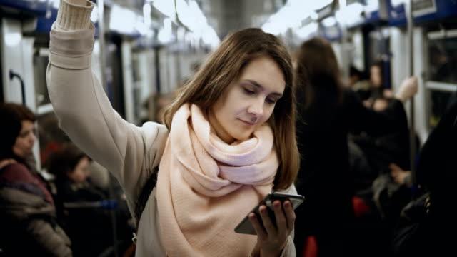 Mujer-hermosa-joven-utiliza-el-smartphone-en-transporte-público-en-metro-Chica-navegando-por-Internet