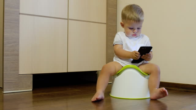 Little-boy-pisses-in-his-potty-and-looks-at-the-telephone