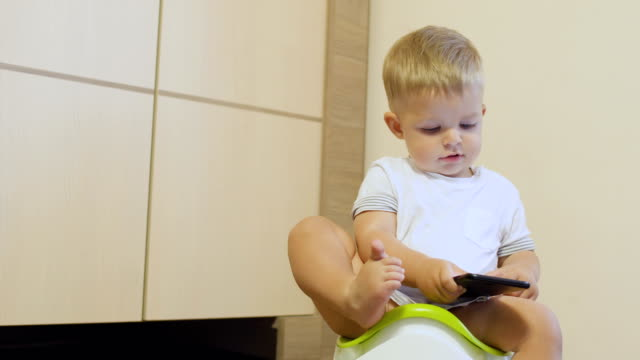 Cute-little-boy-plays-with-phone-sitting-on-the-potty