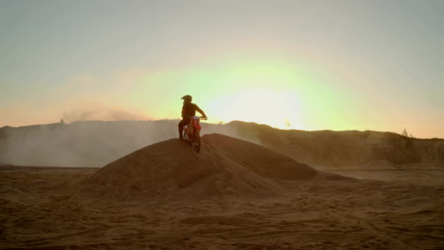 Long-Shot-Of-the-Extreme-Motocross-Rider-in-a-Cool-Protective-Helmet-Standing-on-the-Sand-Dune-in-the-Middle-of-Scenic-Quarry-with-Mist-and-Dust-Covering-Him-