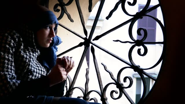 sad-woman-suffering-from-cancer-at-the-window-greets-someone-feebly