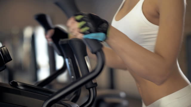 Portrait-fitness-woman-warm-up-before-training-on-elliptical-cross-trainer