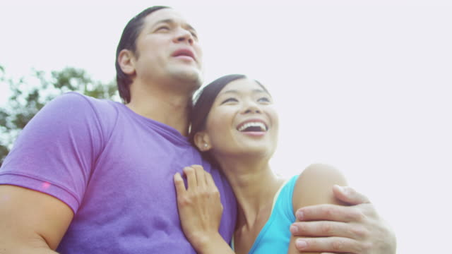 Young-male-female-ethnic-couple-laughing-together-outdoors