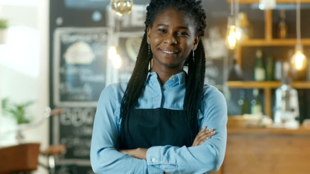 Beautiful-African-American-Cafe-Owner-Standing-with-Crossed-Arms-and-a-Smile-in-Her-Stylish-Coffee-House-