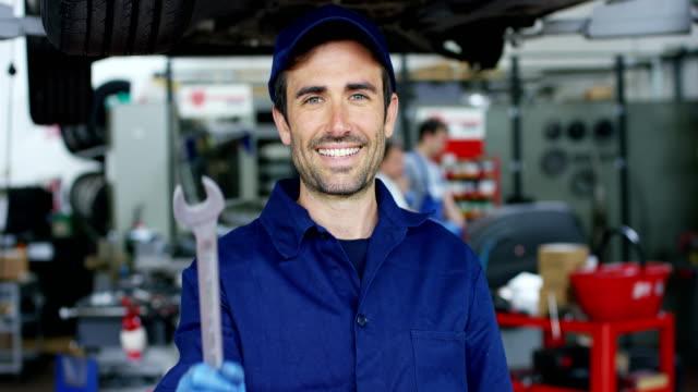 Retrato-de-un-joven-mecánico-hermosa-en-un-taller-de-coches-en-el-fondo-del-servicio-Concepto:-reparación-de-máquinas-diagnóstico-de-fallas-reparación-especialista-mantenimiento-técnico-y-ordenador-de-a-bordo