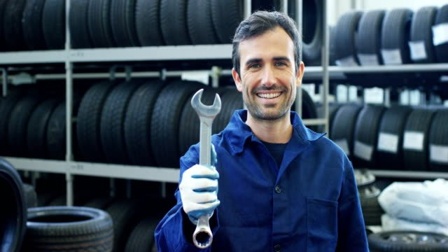 Portrait-of-a-young-beautiful-car-mechanic-in-a-car-service-in-the-background-of-rubber-Concept:-repair-of-machines-fault-diagnosis-repair-specialist-technical-maintenance-and-on-board-computer-