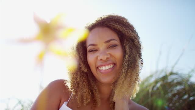 Portrait-of-African-American-female-blowing-flower-windmill