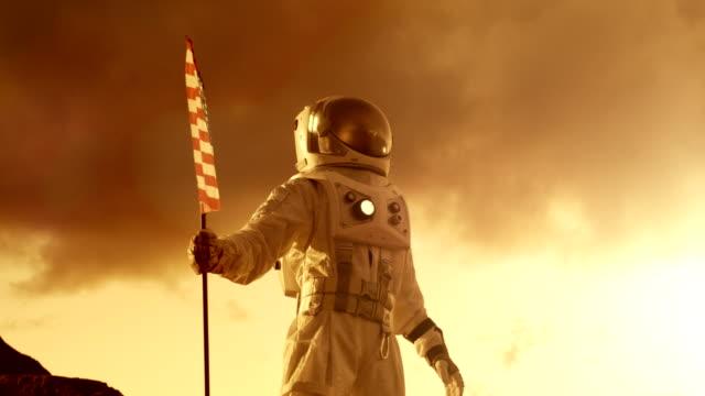 Astronauta-con-traje-espacial-planta-la-bandera-estadounidense-en-el-planeta-rojo-/-Marte-mira-hacia-el-horizonte-Momento-patriótico-y-orgullo-para-toda-la-humanidad-Recorrido-de-espacio-y-concepto-de-colonización-