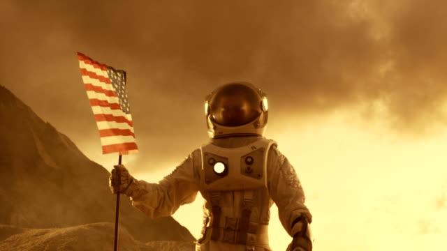 Caminatas-fuertes-de-astronauta-en-Marte-con-una-bandera-de-une-Estados-de-América-con-plantas-en-la-superficie-del-planeta-rojo-Recorrido-de-espacio-tema-de-la-colonización-