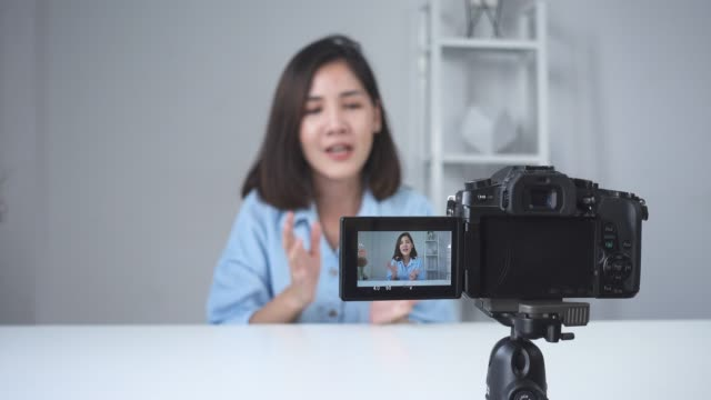 Happy-smiling-asian-woman-or-beauty-blogger-with-brush-and-camera-recording-video-and-waving-hand-at-home-Beauty-videoblog-blogging-people-concept-Dolly-shot-
