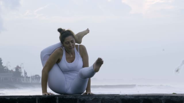 Woman-Practicing-Yoga-on-Pier