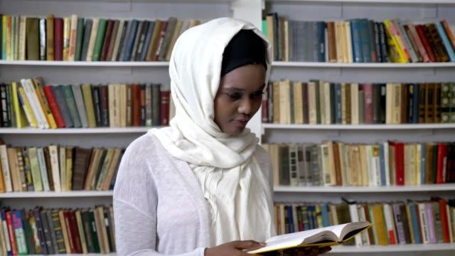 Niña-musulmana-africana-en-hijab-es-sosteniendo-un-libro-mirando-a-cámara-religioun-concepto-booksheves-en-el-fondo