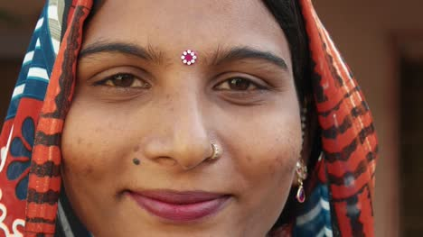 Extreme-close-up-of-a-gorgeous-Indian-woman-s-face-smiling-laughing-happy-joy-jovial-looking-at-camera-in-traditional-dress-head-covered-bindi-pretty-jewelry-at-home-freedom-love-static-shot-lock-down