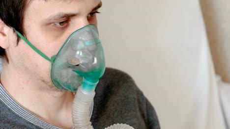 Use-nebulizer-and-inhaler-for-the-treatment-Closeup-man-s-face-inhaling-through-inhaler-mask-Front-view-