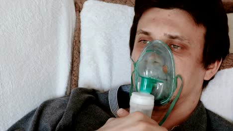 Use-nebulizer-and-inhaler-for-the-treatment-Closeup-man-s-face-inhaling-through-inhaler-mask-lying-on-the-couch-Front-view