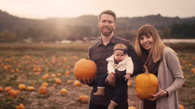 Portrait-of-a-young-family-at-a-pumpkin-patch-mom-and-dad-holding-pumpkins-with-lens-flare