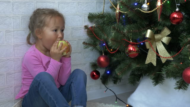 Cute-little-girl-sitting-on-the-floor-and-eating-apple-next-to-a-Christmas-tree-