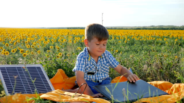 child-using-solar-battery-recharges-laptop-on-background-field-of-sunflowers-happy-kid-looks-at-notebook-with-solar-charger