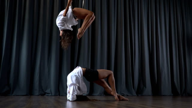 Pretty-girl-makes-a-tricks-on-aerial-hoop-and-her-friend-warms-up-on-floor