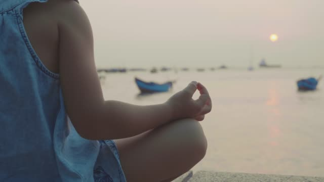 Little-cute-girl-meditates-in-turkish-pose-at-seafront