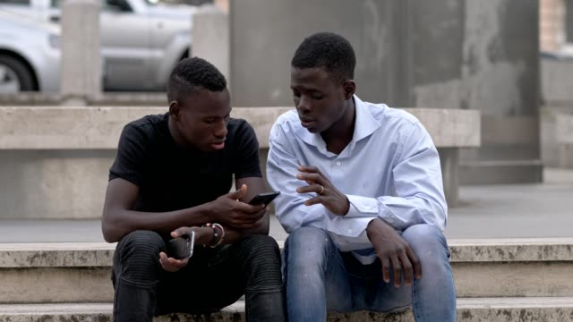 young-black-African-friends-talking-with-cellphones-in-hands---outdoor