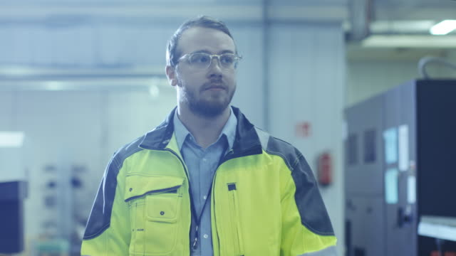 Industrial-Engineer-Wearing-Protective-Clothing-Puts-on-Hard-Hat-and-Walks-Through-Modern-Manufacturing-Facility-with-Automatic-Machinery-Working-in-Background-