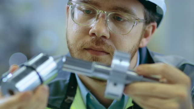 Close-up-Shot-of-the-Industrial-Engineer-Wearing-Classes-and-Hard-Hat-Connects-Two-Components-He-Designed-Precision-in-Mechanical-Engineering-