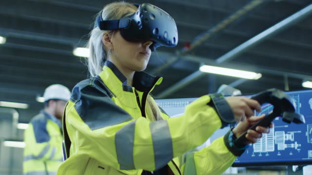 Factory:-Female-Industrial-Engineer-Wearing-Virtual-Reality-Headset-and-Holding-Controllers-She-Uses-VR-technology-for-Industrial-Design-Development-and-Prototyping-in-CAD-Software-
